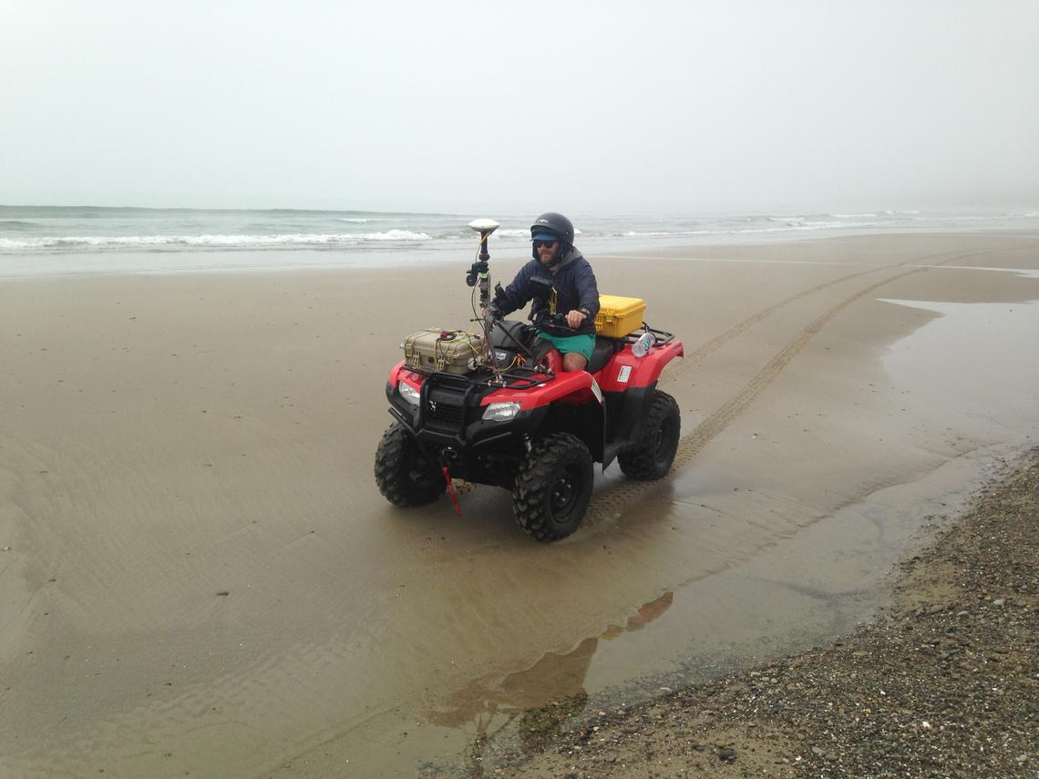 Man wearing a safety helmet rides an all-terrain vehicle with equipment on it, driving on a flat beach on wet sand and pebbles.