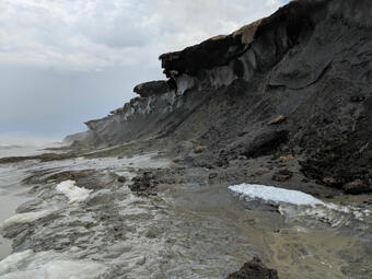 View of muddy, eroding coastal bluffs with a visible permafrost layer and tumbling tundra on top.