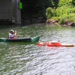 man sitting in green canoe on water paddling behind an orange floating object