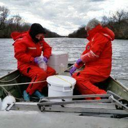 2 people in red cold weather flotation suits on boat in river qw sampling