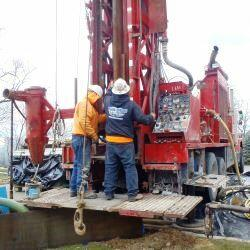 2 men working on drill rig on back of truck