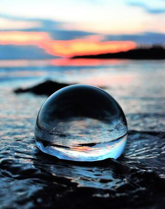 A glass ball showing a scene of the ocean in it.